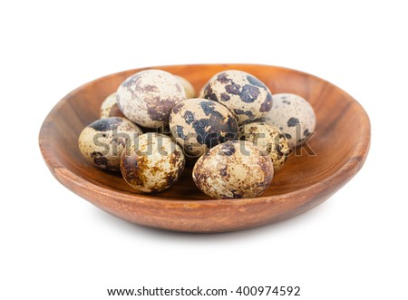 Quail eggs in wood plate isolated