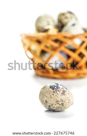 Quail eggs on wooden plate on white background. - stock photo