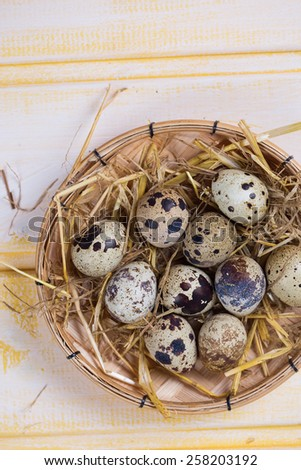 Quail eggs on yellow  wooden background. Selective focus. - stock photo