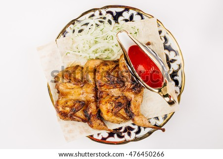 quail grilled with sauce on a plate on a white background. food and healthy eating concept