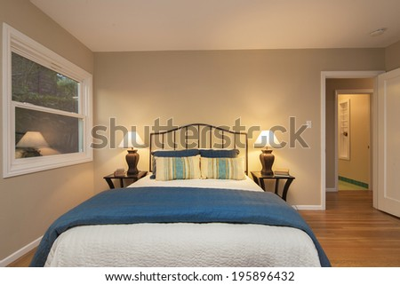 Quaint Bedroom at twilight in beige with bedside lamps and vintage furniture. - stock photo