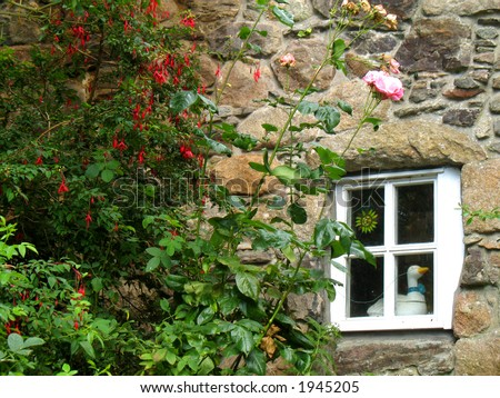 Quaint stone cottage wall with flowers and window - stock photo