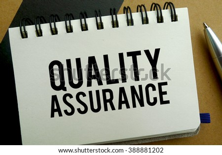 Quality assurance memo written on a notebook with pen