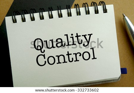 Quality control memo written on a notebook with pen
