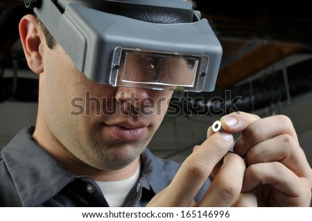 Quality Inspector wearing magnifying glasses inspecting a small manufactured part - stock photo