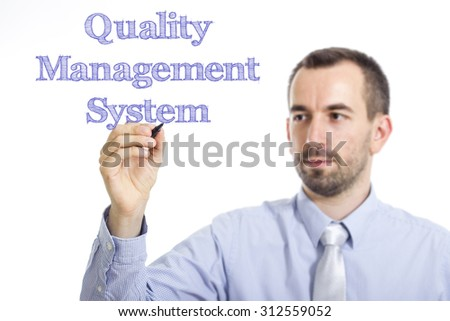 Quality Management System QMS - Young businessman writing blue text on transparent surface
