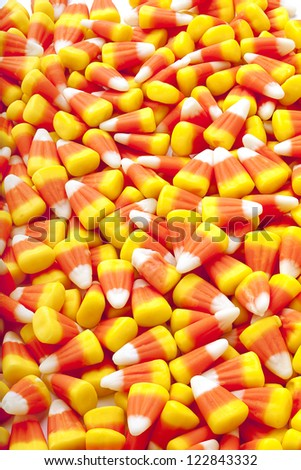 Quantities of candy corn scattered on floor. - stock photo