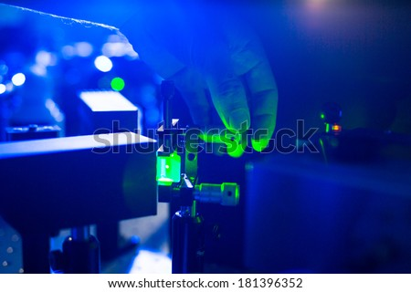 Quantum optics - hand of a researcher adjusting a laser beam in a lab - stock photo
