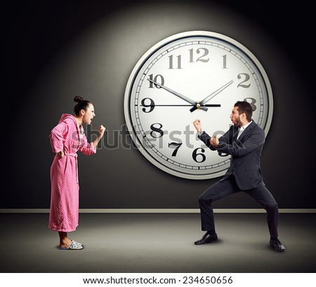 quarrel between emotional couple over wall with big clock - stock photo