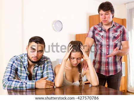 Quarrel in adult polygamous family indoors. Focus in the couple