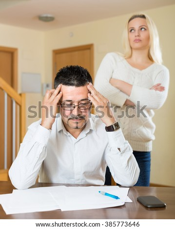Quarrel in family over financial documents at home. Focus on man - stock photo