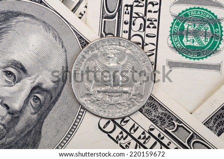 Quarter dollar coin lies on top of hundred dollars banknotes. - stock photo