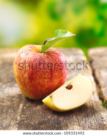Quartered apple showing juicy the juicy flesh together with a whole fruit on an old textured wooden table outdoors - stock photo