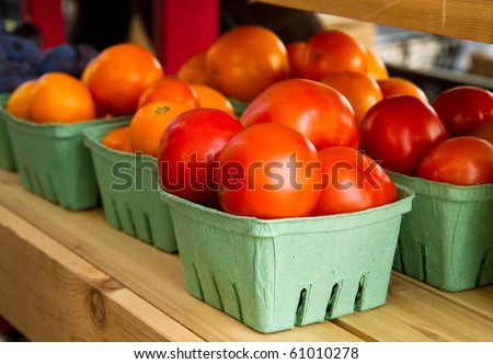 Quarts of late summer tomatoes on a shelf at a farmer's market - stock photo
