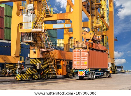 Quay crane loading container from container ship to container truck for transportation - stock photo