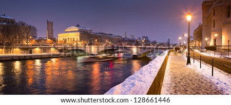 Quayside along River Seine in Paris, France, at night under snow.