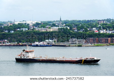 QUEBEC CITY, CANADA - JULY, 20: Large oil tanker in front of Quebec city in July 2014. Twenty-five million tonnes of crude oil and various petroleum products are transported on the St.Lawrence seaway - stock photo