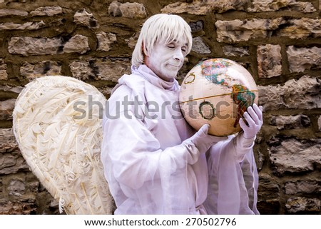 Quebec Town, Quebec,Canada-July 1-2012 Street entertainer: That angel man in white, holding a earth globe.  - stock photo