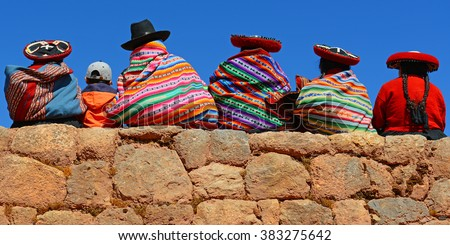 Quechua ladies and a young boy chatting on an ancient Inca wall. - stock photo