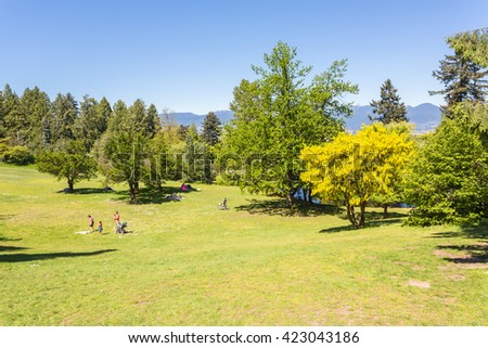 Queen Elizabeth park, Vancouver, Canada. People relaxing on the grass. - stock photo