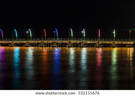 Queen Emma pontoon bridge illuminated with colourful lights at night in Willemstad, Curacao.