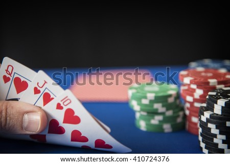 Queen, Jack, Ten in hand and gambling chips on casino blue felt - stock photo