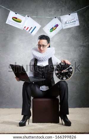 Queen of office. Business lady in ruff collar with a clock using laptop - stock photo