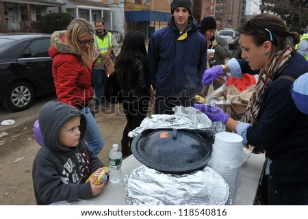 QUEENS, NY - NOVEMBER 11: People getting help with hot food, clothes and supplies in the Rockaway beach area due to impact from Hurricane Sandy in Queens, New York, U.S., on November 11, 2012. - stock photo