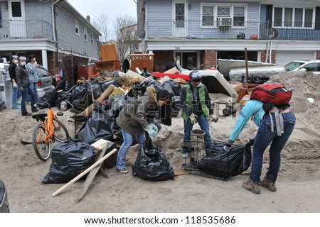 QUEENS, NY - NOVEMBER 11: Volunteers cleaning debris and sand in the Rockaway beach residential area from Hurricane Sandy in Queens, New York, U.S., on November 11, 2012. - stock photo