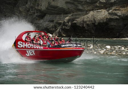 QUEENSTOWN, NEW ZEALAND - DECEMBER 28: Tourists enjoy a high-speed boat ride on Queenstown's Shotover river on December 28, 2012 in Queenstown, New Zealand. Queenstown is a popular alpine resort. - stock photo