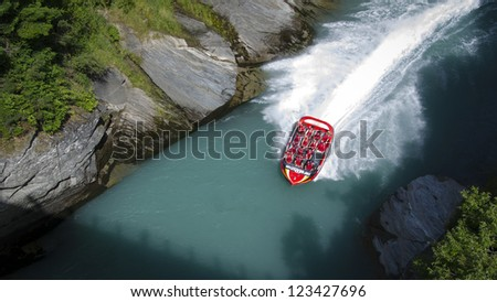 QUEENSTOWN, NEW ZEALAND - DECEMBER 28: Tourists enjoy a high speed jet boat ride on the Shotover River on December 28, 2012 in Queenstown, New Zealand. Queenstown is a popular summer resort. - stock photo