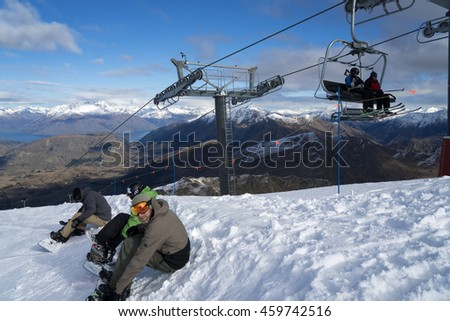 QUEENSTOWN, NEW ZEALAND - JULY 26: Unidentified skiers and snowboarders enjoying early season snow and great views on Coronet Peak ski field on July 26 2016 in Queenstown, South Island, New Zealand - stock photo