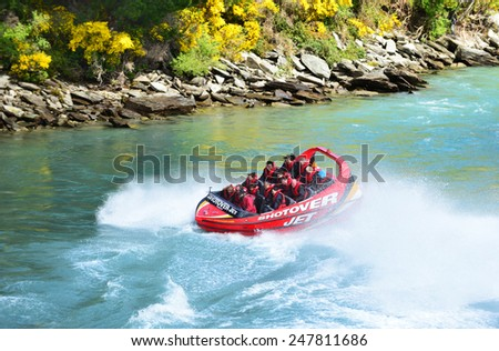 QUEENSTOWN, NEW ZEALAND - November 18: Tourists enjoy a high-speed boat ride on Queenstown's Shotover river on November 18, 2014 in Queenstown, New Zealand. Queenstown is a popular alpine resort. - stock photo