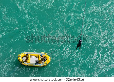 Queenstown, New Zealand - October 11: AJ Bungy's crew on rubber boat use long stick to grab their customer after bungy jump from the Kawarau Bridge on October 11, 2015 in Queenstown, New Zealand - stock photo