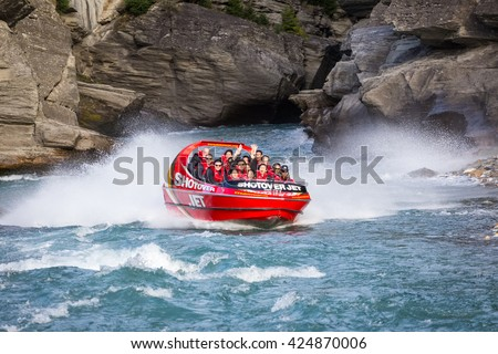 QUEENSTOWN,NZ - APR 10: Tourists enjoy a high speed jet boat ride on the Shotover River on April 10, 2016 in Queenstown, New Zealand. Queenstown is one of the most popular summer resort in NZ. - stock photo