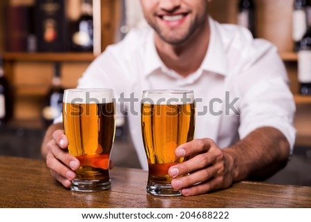 Quench your thirst! Close-up of handsome young male bartender in white shirt stretching out glasses with beer and smiling while standing at the bar counter  - stock photo