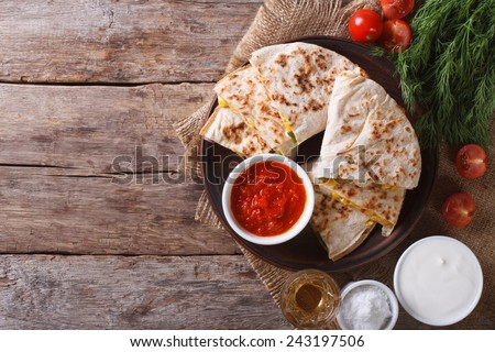 Quesadilla sliced with vegetables and sauces on the table. horizontal view from above  - stock photo