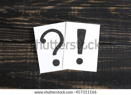 Question and exclamation mark on the paper a few pieces of paper on a wooden table - stock photo