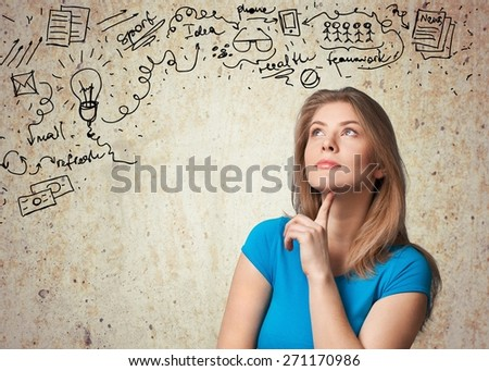 Question. Beautiful girl with questions thinks above her head looking up isolated on grey background - stock photo