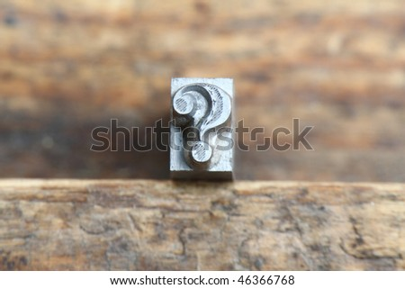 question mark in letterpress type on a wooden background. - stock photo