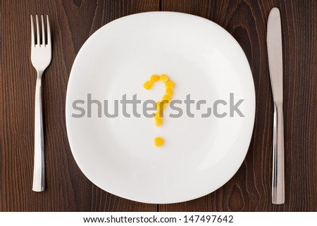 Question mark made of corn seeds on plate - stock photo