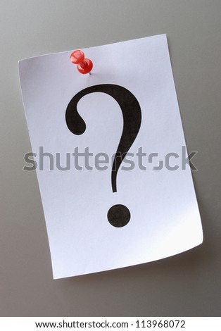 question mark on a piece of paper and a red pushpin - stock photo