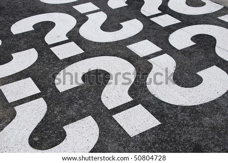 question mark signs painted on a asphalt road surface - stock photo