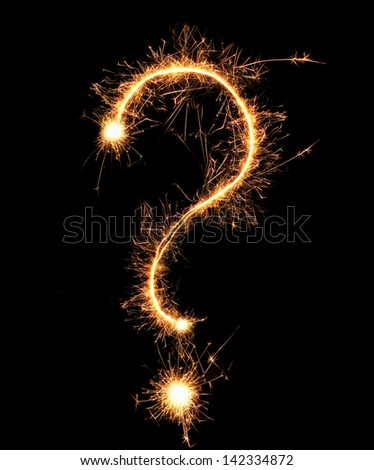 Question mark sparklers on black background - stock photo