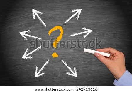 Question mark with arrows and hand on chalkboard background - stock photo