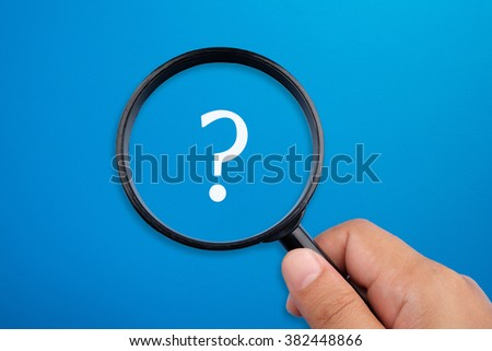 Question marks symbol. Hand holding magnifying glass focusing on the symbol. - stock photo