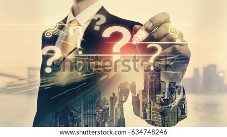 Question Marks with double exposure of businessman and big city
