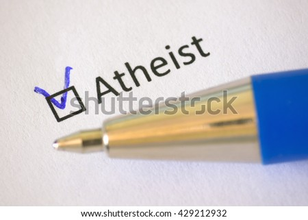 Questionnaire blue pen and the inscription ATHEIST with check mark on the white paper