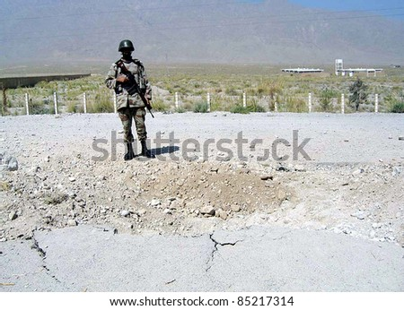 QUETTA, PAKISTAN - SEPT 23: A FC soldier stands alert at the site of explosion while broken portion of road also seen in picture after bomb explosion on September 23, 2011 in Quetta .