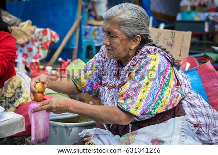 Quetzaltenango, Guatemala - February 8, 2015: Maya woman sells sweet deep fried bunuelos at a local food market in Xela, Guatemala. Central America